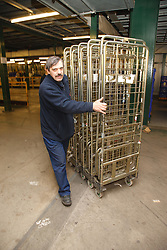 Man with a mild learning disability working as a factory operative, shown here moving trolleys, helped into employment by the Ready 4 Work team, Nottinghamshire County Council
