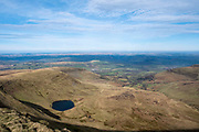 Landscape view from the summit of Pen Y Fan towards Llyn Cwm Llwch glacial lake and across the Brecon Beacons National Park, Wales, Powys, United Kingdom. Pen Y Fan is the highest point in the Brecon Beacons hill and mountain range in South Wales. The National Park was established in 1957 due to the spectacular landscape which is rich in natural beauty.