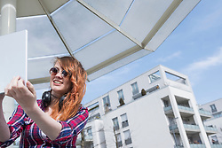 Young woman taking selfie with digital tablet, Munich, Bavaria, Germany