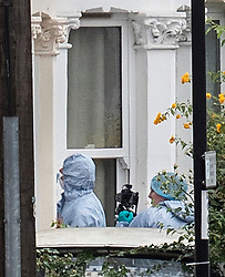 © Licensed to London News Pictures. 18/08/2018. Catford, UK. Investigators in protective suits gather evidence outside a property where a man in his 50's has been stabbed to death in Catford, south London. Police were called at 4am, the victim was pronounced dead at the scene at 5.28am. No arrests have been made. Photo credit: Peter Macdiarmid/LNP