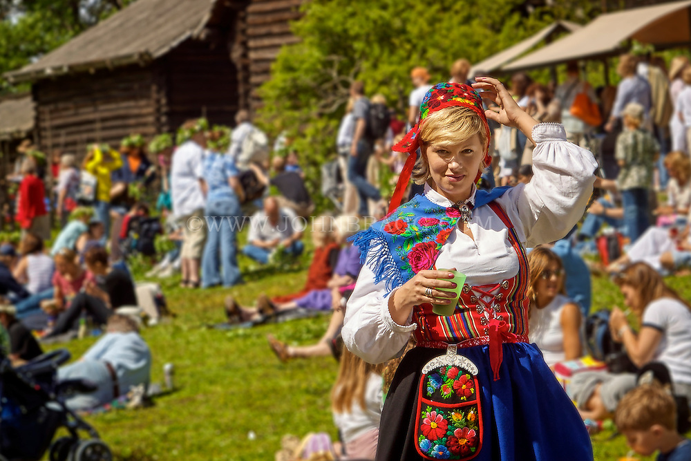 A Swedish woman is wearing a traditional Swedish dress while enjoying the festivities during the mid-summer festival in Stockholm, Sweden.