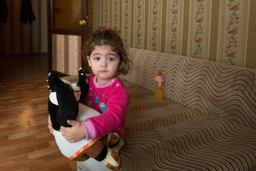 """CAPTION: Stella's mother Armena says that her elder daughter Safira understands that her sister is different to her. """"She often looks at her attentively"""", she explains, """"and there've been times when she's asked what happened to her"""". LOCATION: Volgograd, Russia. INDIVIDUAL(S) PHOTOGRAPHED: Safira Aharonyan."""
