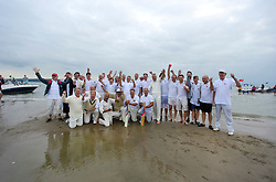 © Licensed to London News Pictures. 18/09/2016. Portsmouth, UK. The two teams pose for a photograph after the game. Teams take part in the  Bramble Bank Cricket Match in the middle of The Solent strait on September 18, 2016. The annual cricket match between the Royal Southern Yacht Club and The Island Sailing Club, takes place on a sandbank which appears for 30 minutes at lowest tide. The game lasts until the tide returns. Photo credit: Ben Cawthra/LNP