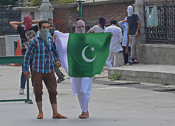 August 4, 2017 - India - A Pro freedom protester displays green flag in old city Srinagar the summer capital of Indian controlled Kashmir on August 04, 2017. The prayers were offered at historic grand mosque after remaining closed for six consecutive weeks. Government authorities had disallowed prayers in the mosque after the recent killings across Kashmir. Soon after the Friday prayers ended pro freedom protesters pelted stones at Indian police who were later dispersed after police fired teargas and pellets. (Credit Image: © Faisal Khan/Pacific Press via ZUMA Wire)