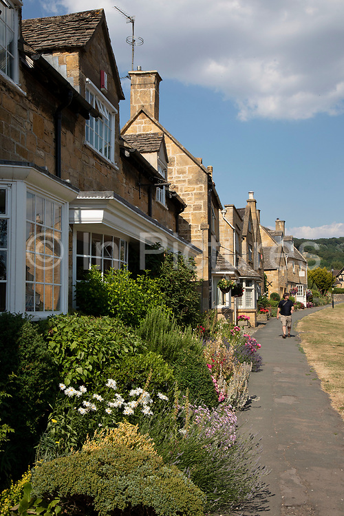 Broadway in The Cotswolds, United Kingdom. Broadway village lies beneath Fish Hill on the western Cotswold escarpment. The 'broad way' is the wide grass-fringed main street, centred on the Green, which is lined with red chestnut trees and honey-coloured Cotswold limestone buildings, many dating from the 16th century. It is known for its association with the Arts and Crafts movement, and is situated in an area of outstanding scenery and conservation. The wide High Street is lined with a wide variety of shops and cafes, many housed in listed buildings. The Cotswolds is an area in south central England. The area is defined by the bedrock of limestone that is quarried for the golden coloured Cotswold stone. It contains unique features derived from the use of this mineral; the predominantly rural landscape contains stone-built villages and historical towns.