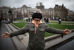 """© Licensed to London News Pictures . 05/12/2015 . Manchester , UK . Members of the public are invited to hug a blindfolded refugee , in a separate action organised by """" RAPAR """" . Approximately one hundred anti-war protesters march through central Manchester against Parliament's decision to vote in favour of bombing against """" ISIS """" , in Syria . Photo credit : Joel Goodman/LNP"""