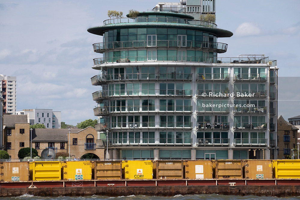 Downstream waste barges operated by Cory Riverside pass riverside properties at Wapping, on 11th June 2021, in London, England. Cory Riverside Energy operates a fleet of five tugs, with over 50 barges and 1,500 containers. Each barge can carry 20 waste containers, containing a total of 270 tonnes of residual waste and the fleet is used to transport residual waste from waste transfer stations along the River Thames to its Belvedere EfW plant. The river traffic removes around 100,000 vehicle journeys from London's roads.