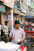 A man sells daulat ki chaat - a fabled sweet - on the streets, Old Delhi, India