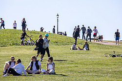 © Licensed to London News Pictures. 19/04/2020. London, UK. Members of the public enjoy a walk on a warm Spring day as Police vans patrol Primrose Hill enforcing lockdown rules on social distancing and exercise as Ministers urge councils to keep parks open to the public during lockdown. Photo credit: Alex Lentati/LNP