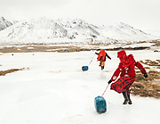 Kyrgyz girls slide large plastic jerry cans back to their family's camp after hacking a hole in the frozen river to fetch water. Men handle herding and trading; much of the hard labor of daily life falls to the women.<br /> <br /> The Kyrgyz settlement of Tchelab, near Chaqmaqtin lake, Haji Bootoo Boi's camp.<br /> <br /> Trekking through the high altitude plateau of the Little Pamir mountains, where the Afghan Kyrgyz community live all year, on the borders of China, Tajikistan and Pakistan.
