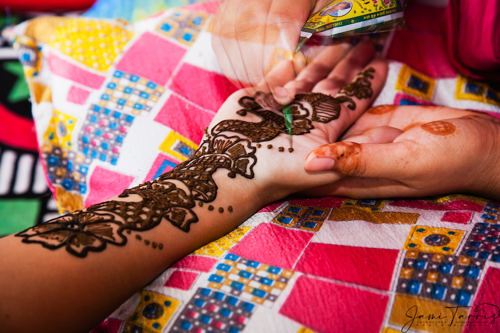 A close-up of a henna tattoo being painted on a girls arm and hand in the blue city of Jodphur, Jodphur Rajasthan, India