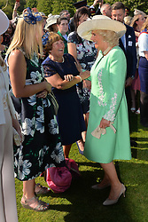 The Duchess of Cornwall (right) speaks with guests during a garden party at Buckingham Palace in London.
