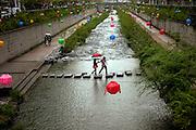 Der Cheonggyechon wurde in den 60er Jahren durch eine mehrspurige Strasse verdeckt. Inzwischen hat jedoch auch die Stadt Seoul den Wert von Gr¸nfl‰chen erkannt und in einem aufwendigen Projekt die (ohnehin mit Sicherheitsm‰ngeln behaftete) Strasse wieder entfernt. Entstanden ist ein neuer, nun allerdings k¸nstlicher Fluss quer durch das Zentrum der Stadt, dessen Wege zu einem Spaziergang einladen. F¸r die Feierlichkeiten von Buddhas Geburtstag (2. Mai diesen Jahres) wurde der Bereich mit bunten Lampions dekoriert.<br /> <br /> Cheonggyecheon is a nearly 6 km long, modern public recreation space in downtown Seoul, South Korea. The massive urban renewal project is on the site of a stream that flowed before the rapid post-war economic development required it to be covered by transportation infrastructure. The $900 million project attracted much criticism initially but opened in 2005 and is now popular among Seoul residents and tourists. For the celebration of Buddhas birthday (2nd of May this year) the area was decorated with colorful lampions.