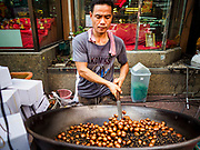 """18 MAY 2017 - BANGKOK, THAILAND: A man roasts chestnuts on Yaowarat Road in Bangkok. City officials in Bangkok have taken steps to rein in street food vendors. The steps were originally reported as a """"ban"""" on street food, but after an uproar in local and international news outlets, city officials said street food vendors wouldn't be banned but would be regulated, undergo health inspections and be restricted to certain hours on major streets. On Yaowarat Road, in the heart of Bangkok's touristy Chinatown, the city has closed some traffic lanes to facilitate the vendors. But in other parts of the city, the vendors have been moved off of major streets and sidewalks.      PHOTO BY JACK KURTZ"""