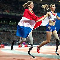 Engeland, Londen, 02-09-2012.<br /> Paralympische Spelen.<br /> Atletiek, Vrouwen, 100 meter T44, Finale.<br /> Marlou van Rhijn uit Nederland ( links ) die zilver won en Marie-Amelie le Fur uit Frankrijk die goud won maken samen een ereronde in een volgepakt Olympisch Stadion.<br /> Foto : Klaas Jan van der Weij