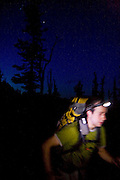 Brian Polagye hikes past at night wearing a headlamp on the trail to Ingalls Lake,  Alpine Lakes Wilderness, Washington.