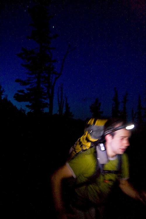 Brian Polagye hikes past at night wearing a headlamp on the trail to Ingalls Lake,  Alpine Lakes Wilderness, Washington.