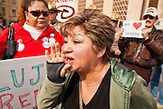 23 JANUARY 2012 - PHOENIX, AZ:     An opponent of SB 1070 shouts at pro-1070 demonstrators at the State Capitol Monday, Jan 23. Both sides of the immigration debate congregated on the capitol grounds to protest against and in favor of SB 1070 and other anti immigration bills. At the same time people were protesting, legislators from both sides of the issue held press conferences.    PHOTO BY JACK KURTZ