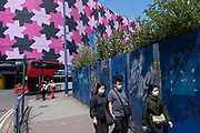 People wearing face masks pass a blue hoarding around the construction site where a new high rise development, the Beorma Quarter, will be situated near the iconic Selfridges building on 14th July 2021 in Birmingham, United Kingdom. This site, part of the city centre redevelopment has stalled in recent months and currently sits quiet and with plants overgrowing its graffiti covered perimeter.