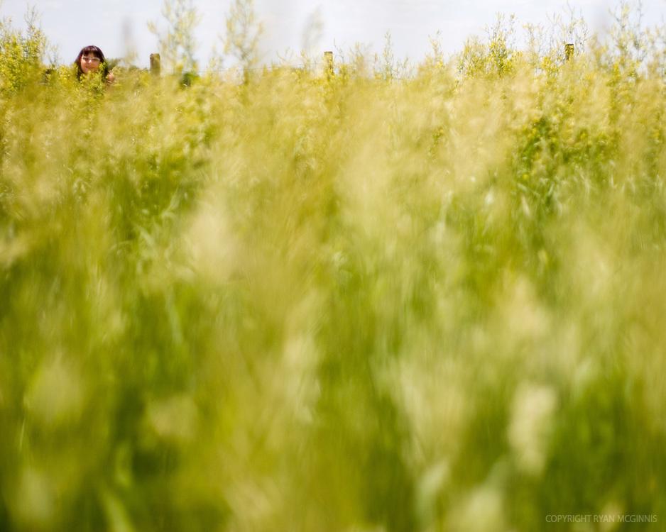 A woman crouches in tallgrass.