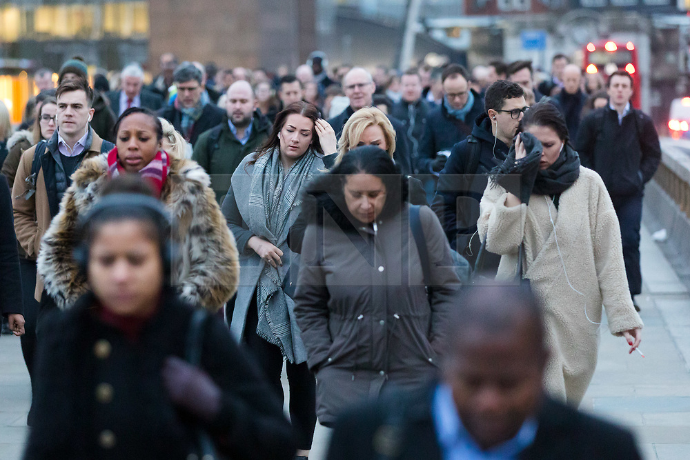 © Licensed to London News Pictures. 07/01/2019. London, UK.  Commuters walk to work across London Bridge this morning on 'Blue Monday'. Psychologists claim that a number of factors including the weather and post Christmas debt statistically make today the most depressing day of the year. Photo credit: Vickie Flores/LNP