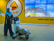 "23 FEBRUARY 2016 - BANGKOK, THAILAND:   A woman walks by a Nok Air electronic billboard in the domestic terminal at Don Mueang Airport. Nok Air, partly owned by Thai Airways International and one of the largest and most successful budget airlines in Thailand, cancelled 20 flights Tuesday because of a shortage of pilots and announced that other flights would be cancelled or suspended through the weekend. The cancellations came after a wildcat strike by several pilots Sunday night cancelled flights and stranded more than a thousand travelers. The pilot shortage at Nok comes at a time when the Thai aviation industry is facing more scrutiny for maintenance and training of air and ground crews, record keeping, and the condition of Suvarnabhumi Airport, which although less than 10 years old is already over capacity, and facing maintenance issues related to runways and taxiways, some of which have developed cracks. The United States' Federal Aviation Administration late last year downgraded Thailand to a ""category 2"" rating, which means its civil aviation authority is deficient in one or more critical areas or that the country lacks laws and regulations needed to oversee airlines in line with international standards.       PHOTO BY JACK KURTZ"