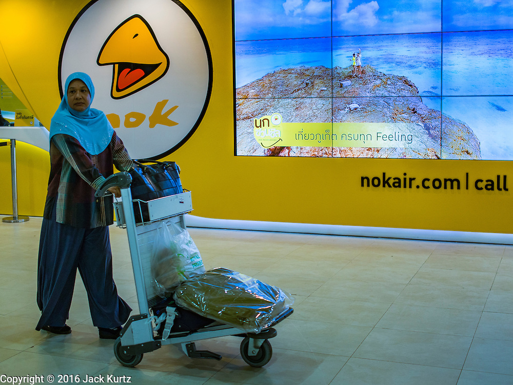 """23 FEBRUARY 2016 - BANGKOK, THAILAND:   A woman walks by a Nok Air electronic billboard in the domestic terminal at Don Mueang Airport. Nok Air, partly owned by Thai Airways International and one of the largest and most successful budget airlines in Thailand, cancelled 20 flights Tuesday because of a shortage of pilots and announced that other flights would be cancelled or suspended through the weekend. The cancellations came after a wildcat strike by several pilots Sunday night cancelled flights and stranded more than a thousand travelers. The pilot shortage at Nok comes at a time when the Thai aviation industry is facing more scrutiny for maintenance and training of air and ground crews, record keeping, and the condition of Suvarnabhumi Airport, which although less than 10 years old is already over capacity, and facing maintenance issues related to runways and taxiways, some of which have developed cracks. The United States' Federal Aviation Administration late last year downgraded Thailand to a """"category 2"""" rating, which means its civil aviation authority is deficient in one or more critical areas or that the country lacks laws and regulations needed to oversee airlines in line with international standards.       PHOTO BY JACK KURTZ"""