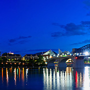 Panorama of Chattanooga's skyline at dusk, with the Walnut Street Bridge at left and the Delta Queen riverboat and John Ross Bridge at right.
