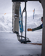 A lift operator reaches out to bump a chair at Monarch Mountain.