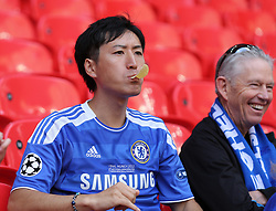 A Chelsea fan eats a crisp in the stands before the match against Arsenal
