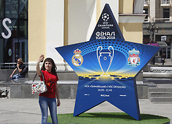 May 18, 2018 - Kiev, Ukraine - An Ukrainian woman takes a selfie near a large sign showcasing the logo for the 2018 UEFA Champions League Final in central Kiev, Ukraine, 18 May, 2018. The football UEFA Champions League final match between Real Madrid and Liverpool FC next May 26 at the NSC Olimpiyskiy Stadium. (Credit Image: © Str/NurPhoto via ZUMA Press)