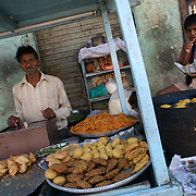A young school boy eating some snacks next to a food stall selling Jalebi, samosa, aloo chaap, and tikkis in Raipur, Chhattisgarh. January 2007