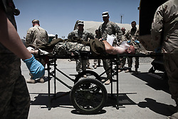 """A soldier whose lower leg has been severely damaged by a RPG in Kandahar's Zhari Province is unloaded from an ambulance at the military hospital at Kandahar Airfield. Scenes from the medical evacuations of wounded Americans, Canadians, and Afghan civilians and soldiers being flown by Charlie Co. 6th Battalion 101st Aviation Regiment of the 101st Airborne Division. Charlie Co. - which flies under the call-sign """"Shadow Dustoff"""" - flies into rush the wounded to medical care out of bases scattered across Oruzgan, Kandahar, and Helmand Provinces in the Afghan south. These images were taken of missions flown out of Kandahar Airfield in Kandahar Province and Camp Dwyer in Helmand Province."""