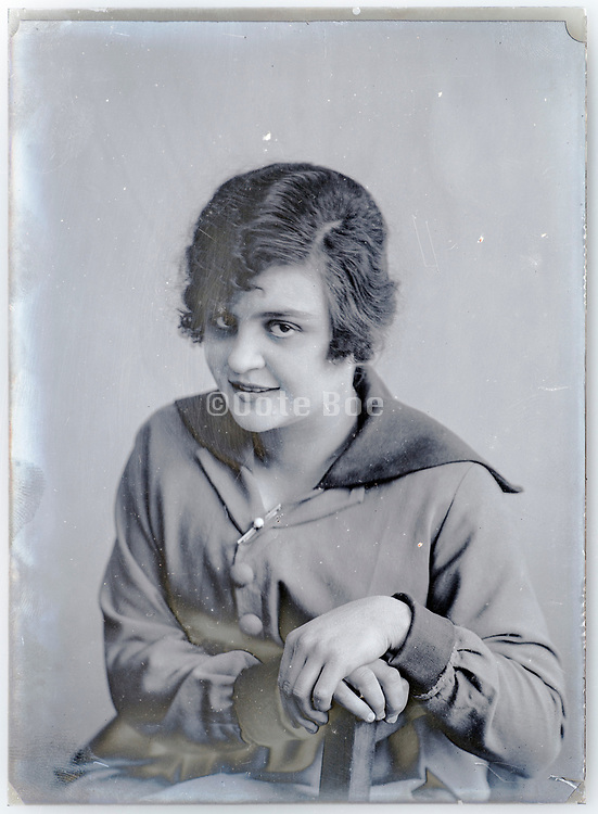 deteriorating glass plate with happy young adult woman looking at the camera circa 1920s
