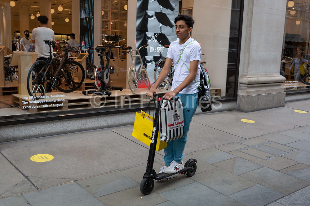 On the day that covid pandemic guidelines for shoppers in England mean that the wearing of face coverings in shops is mandatory, a shopper rides his eScooter past Selfridges, on 24th July 2020, in London, England.