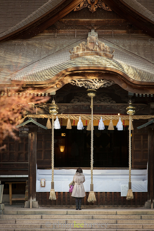 Woman standing by temple, Nagano, Japan