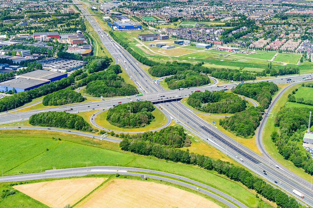 Nederland, Gelderland, Amersfoort, 29-05-2019; Knooppunt Hoevelaken, verkeersknooppunt (klaverblad), aansluiting van de autosnelwegen A28 (links-rechts) en A1 . Links bedrijventerrein De Hoef,  rechts Vathorst.<br /> Hoevelaken junction, near Amersfoort<br /> <br /> <br /> aerial photo (additional fee required); luchtfoto (toeslag op standard tarieven); copyright foto/photo Siebe Swart