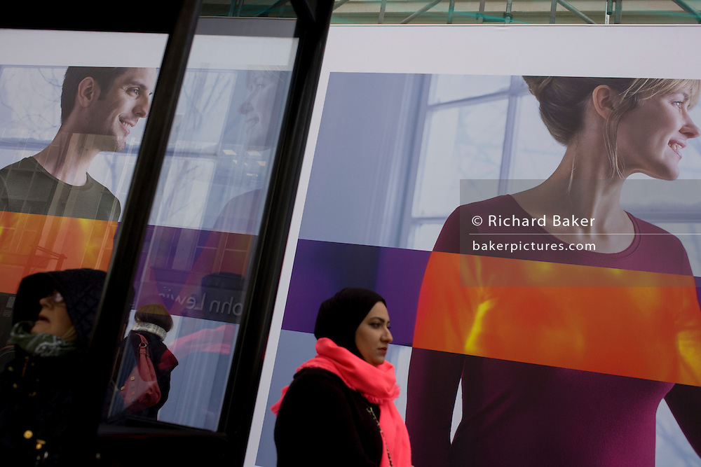 Large models appear on a construction hoarding for clothing retailer Uniglo in central London.
