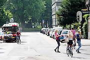 Nederland, Utrecht, 22-07-2015<br /> Een fietser rijdt tussen twee vrouwen door die oversteken in de Burgermeester Reigerstraat in Utrecht, een van de drukste straten met fietsers in Nederland.<br /> <br /> The Burgemeester Reigerstraat is one of the busiest streets with bicycles in The Netherlands.<br /> Foto: Bas de Meijer / Hollandse Hoogte