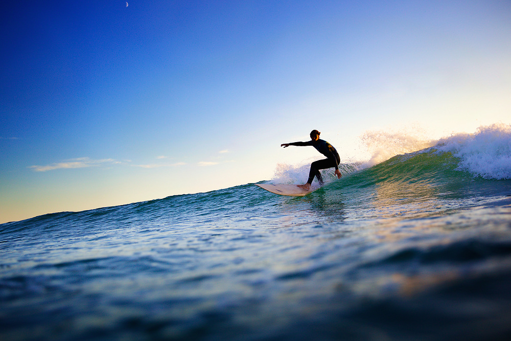 Surfer catching a wave, with the orange light from sunset behind him, at St Ouen's beach, Jersey, Channel Islands