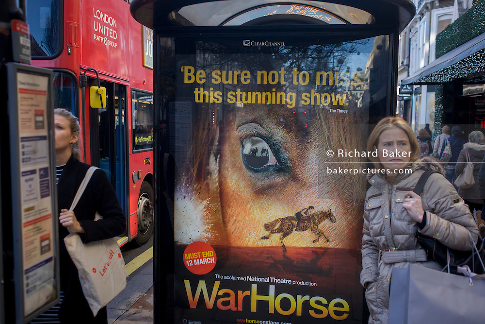 Women shoppers at a bus stop with a War Horse poster in central London