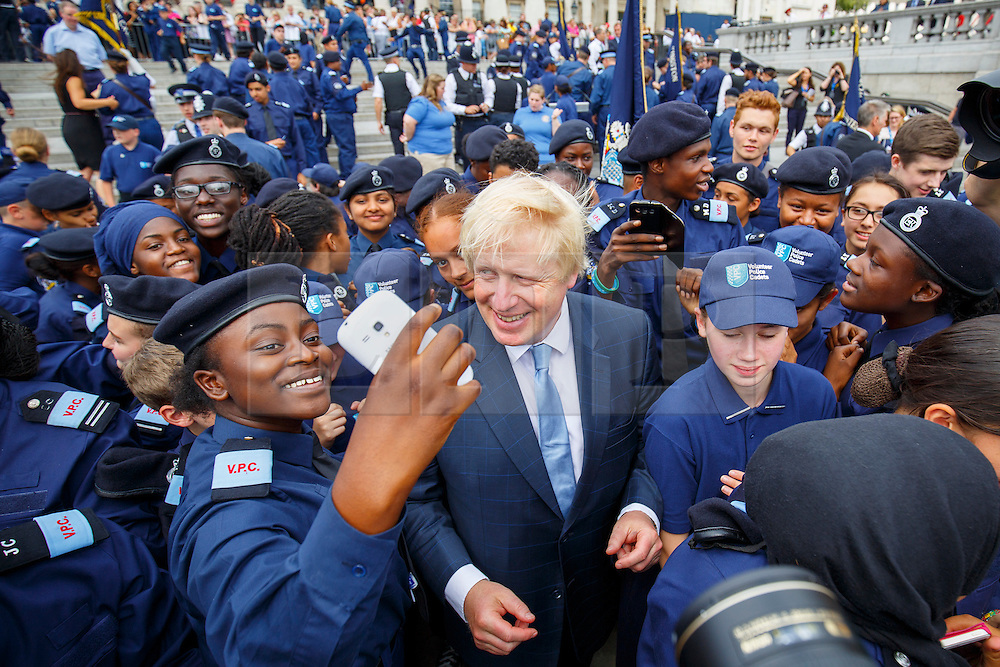 © Licensed to London News Pictures. 03/08/2015. London, UK. Mayor of London, Boris Johnson meeting volunteer police cadets whilst attending a parade for the capital's young police volunteers with Metropolitan Police Commissioner Bernard Hogan-Howe in Trafalgar Square, London on Monday, August 3, 2015. Photo credit: Tolga Akmen/LNP