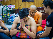 """03 MARCH 2018 - NAKHON CHAI SI, NAKHON PATHOM, THAILAND:  Wat Bang Phra is the best known """"Sak Yant"""" tattoo temple in Thailand. It's located in Nakhon Pathom province, about 40 miles from Bangkok. The tattoos are given with hollow stainless steel needles and are thought to possess magical powers of protection. The tattoos, which are given by Buddhist monks, are popular with soldiers, policeman and gangsters, people who generally live in harm's way. The tattoo must be activated to remain powerful and the annual Wai Khru Ceremony (tattoo festival) at the temple draws thousands of devotees who come to the temple to activate or renew the tattoos. People go into trance like states and then assume the personality of their tattoo, so people with tiger tattoos assume the personality of a tiger, people with monkey tattoos take on the personality of a monkey and so on. In recent years the tattoo festival has become popular with tourists who make the trip to Nakorn Pathom province to see a side of """"exotic"""" Thailand.     PHOTO BY JACK KURTZ"""
