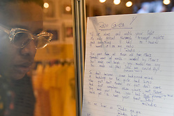 "© Licensed to London News Pictures. 18/10/2018. LONDON, UK. A visitor views Roger Taylor's original handwritten song lyrics to ""Radio Ga Ga"" on display. A Queen pop-up shop has opened in Carnaby Street.  Coinciding with the release next week of the movie ""Bohemian Rhapsody"", the shop offers Queen music fans memorabilia, a display of stage costumes as well as archived Queen performance footage.  Photo credit: Stephen Chung/LNP"
