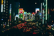 heavy traffic and a full moon over the Shinkjuko district of Tokyo, Japan