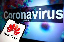The Huawei logo seen displayed on a mobile phone with an illustrative model of the Coronavirus displayed on a monitor in the background. Photo credit should read: James Warwick/EMPICS Entertainment