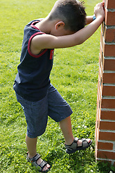 Young boy leaning against wall,