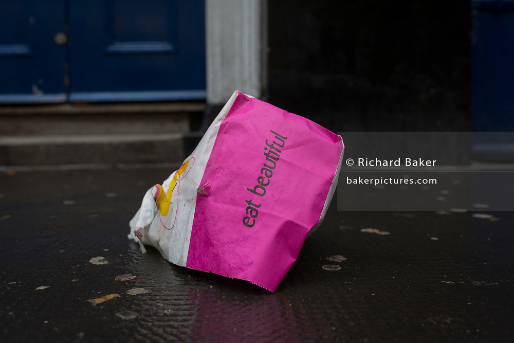 A discarded lunch bag with the words 'Eat Beautiful' on the outside, on 24th January 2018, in Soho, London, England.