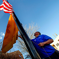 032113  Adron Gardner<br /> <br /> City of Gallup employee Jerry Francis retires the American and New Mexico flags for the day at the corner of Aztec and Second Street in Gallup Thursday.