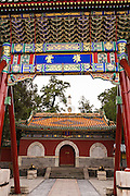 Traditional Chinese decorative archway frames the Chanfu Temple in Beihai Park in Beijing, China